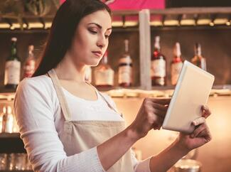 bartender performing weekly inventory counts on a tablet