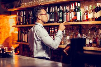 bartender counting inventory behind the bar