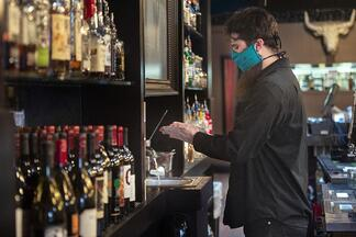 bartender wearing a mask and washing hands to protect against COVID-19