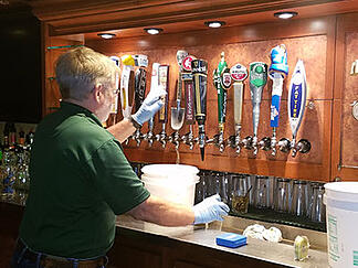 bartender cleaning the draft beer lines
