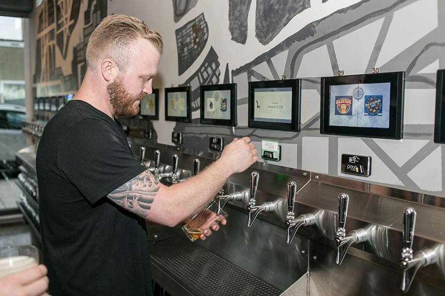 man pouring his own beer at an iPourit self serve draft system