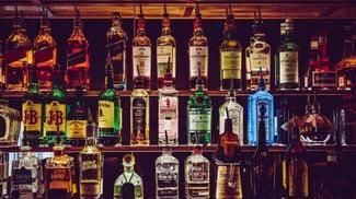 liquor bottles arranged behind the bar so that similar botttles are kept together