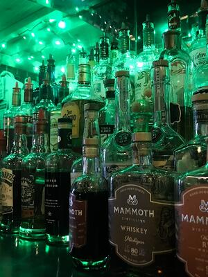 liquor bottles behind a bar before an inventory count is performed