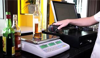 counting bar inventory by weighing bottles on a scale