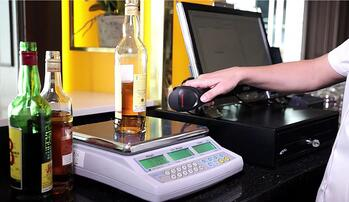 taking inventory of a liquor bottle using a scale and barcode scanner