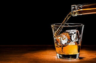 pouring whiskey on the rocks at a high-end bar