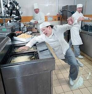 woman slipping and suffering a workplace injury in a restaurant kitchen